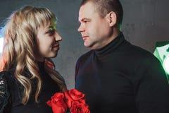 Le couple dans le noir s'habille pendant le tir d'image dans le studio et les projecteurs Images libres de droits