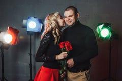 Le couple dans le noir s'habille pendant le tir d'image dans le studio et les projecteurs Photographie stock libre de droits