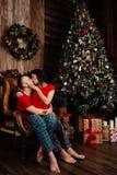 Le couple dans le T-shirts et des pyjamas rouges se repose dans un fauteuil par l'arbre de Noël Photographie stock