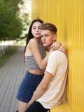 le couple de Chute-dans-amour embrasse sur un fond jaune de mur Début d'une histoire d'amour Sentiments, concept de tendresse Photographie stock libre de droits