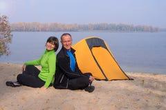 Le couple de hausse heureux se repose dans le camp sur la berge Photographie stock libre de droits