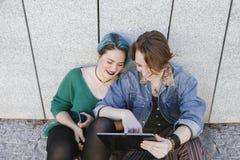 Le couple de jeunes femmes de diversité employant la technologie et riant est Images stock