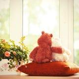 Le couple de l'ours de nounours affectueux joue se reposer sur le fenêtre-filon-couche Images stock