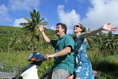 Le couple de lune de miel montant un scooteur dans un Pacifique tropical est Images stock