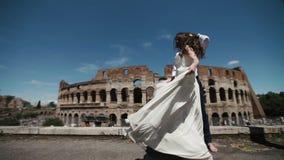 Le couple de mariage à Rome par le Colisé, marié heureux observe sa danse de jeune mariée dans sa longue robe de mariage Lune de  banque de vidéos