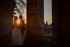 Le couple de nouveaux mariés dans l'amour étreint tendrement parmi de vieilles colonnes pendant le coucher du soleil lumineux Photo stock