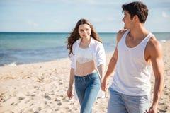 le couple de plage remet la marche de fixation Photos stock