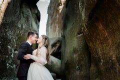 Le couple de sourire de mariage se tient étreignant entre les roches Image stock