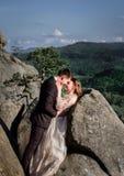 Le couple de sourire de mariage se tient étreignant entre les roches Images stock