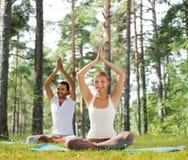 Le couple de sourire faisant le yoga s'exerce dehors Image libre de droits