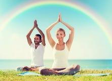 Le couple de sourire faisant le yoga s'exerce dehors Photographie stock libre de droits