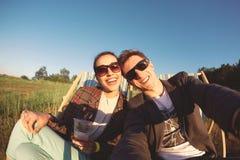 Le couple de sourire fait le selfie et le repos sur la chaise de plate-forme Photo libre de droits