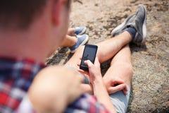 Le couple des amants sourit utilisant leur comprimé pendant le camping - concept au sujet de technologie et de camping Photo libre de droits