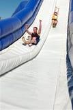 Le couple descend la glissière géante dans le défi de course d'obstacle Image libre de droits