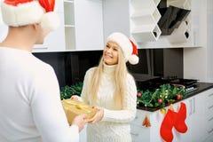 Le couple donne à un cadeau dans une boîte de Noël à l'intérieur la salle Image stock