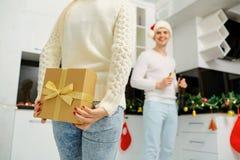 Le couple donne à un cadeau dans une boîte de Noël à l'intérieur la salle Photographie stock libre de droits