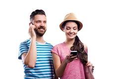 Le couple en été vêtx avec des smartphones, service de mini-messages, appel téléphonique Images libres de droits