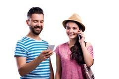 Le couple en été vêtx avec des smartphones, service de mini-messages, appel téléphonique Photographie stock libre de droits