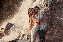 Le couple enamouré par jeunes étreint et des baisers sous le jet de la cascade Photographie stock