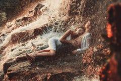 Le couple enamouré par jeunes se trouve sur la roche et étreint sous le jet de l'eau Photos libres de droits