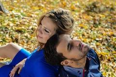 Le couple enceinte de jeunes se reposant sur le jaune part dans le parc Photo libre de droits