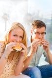 Le couple est affamé et mangeant un hamburger à la rupture Image libre de droits