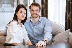 Le couple ethnique différent heureux se repose sur l'entraîneur à la table à la maison Photographie stock