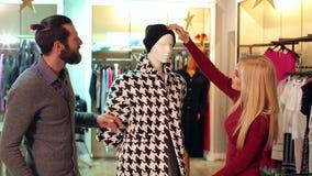 Le couple fait des emplettes ? un magasin d'habillement, ils regarde le manteau sur le mannequin banque de vidéos