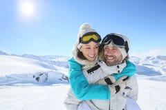 Le couple gai ayant l'amusement sur le ski incline Image stock