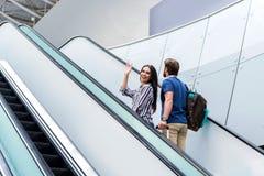Le couple gai est escalier mobile amenant au secteur de départ Photos stock