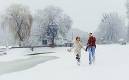 Le couple gai a l'amusement tout en marchant le long du pré neigeux pendant les chutes de neige Temps de Noël Image libre de droits