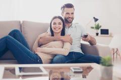 Le couple gai regarde la TV ensemble et a l'amusement Ils sont photographie stock