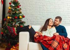 Le couple gentil dans l'amour se trouve sur un divan enveloppé dans Noël E de plaid Photo libre de droits