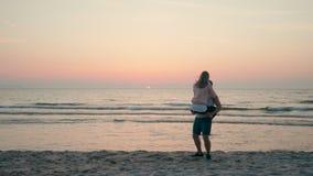 Le couple heureux affectueux est et tourbillonnement riant sur la plage de mer au coucher du soleil en été banque de vidéos