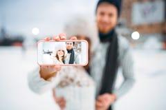 Le couple heureux d'amour fait le selfie sur la piste de patinage Image stock