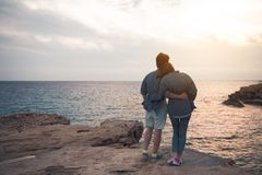 Le couple heureux dans l'amour observe le coucher du soleil Photos libres de droits