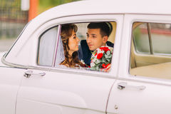 Le couple heureux de nouveaux mariés se repose sur une banquette arrière de voiture de vintage Photo libre de droits