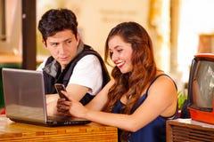 Le couple heureux de sourire à la barre passant le temps ensemble, homme fol regarde et son amie tandis qu'elle l'emploie Photographie stock