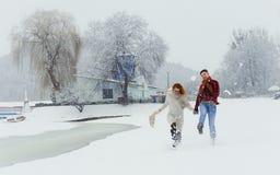 Le couple heureux des amants passe le temps sur le pré neigeux Ils marchent pendant les chutes de neige Conte de fées de Noël Images stock