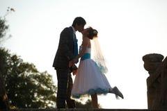 Le couple heureux est étreignant et s'embrassant sur le soleil de fond Photographie stock libre de droits