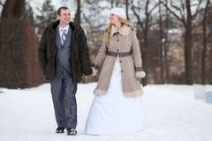 Le couple heureux et souriant de mariage marche ensemble en parc d'hiver, mains de participation Photographie stock