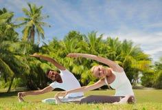 Le couple heureux faisant le yoga s'exerce dehors Image libre de droits
