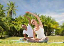Le couple heureux faisant le yoga s'exerce dehors Photo libre de droits