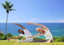 Le couple heureux faisant le yoga s'exerce dehors Images libres de droits