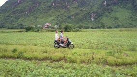 Le couple heureux monte le scooter parmi la vue de côté aérienne de champs banque de vidéos
