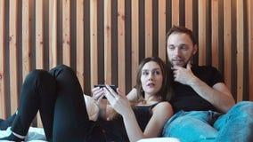Le couple heureux utilise le smartphone aux regards les photos, se trouvant sur le lit Jeune homme et femme parlant, passant le t banque de vidéos