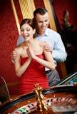 Le couple jouant la roulette est désireux de gagner photographie stock