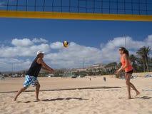 Le couple joue le beachvolleyball photographie stock