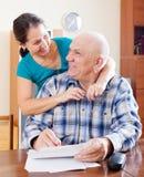 Le couple mûr heureux complète les documents sur papier Image libre de droits