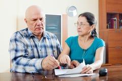 Le couple mûr sérieux complète le questionnaire Photos stock